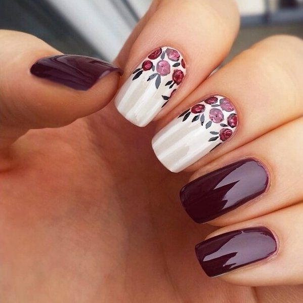 Uñas de color ciruela con diseños de flores en color blanco
