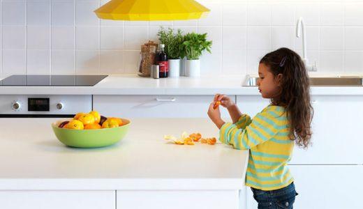 Une jeune fille épluche une orange sur l'ilôt de sa cuisine IKEA