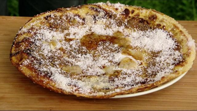 Maak beslag door de bloem en eieren te mengen en daar beetje voor beetje al roerend melk aan toe te voegen. Blijf roeren tot een gladde massa ontstaat. Roer op het laatst de olie erdoor. Zet een bakpan op hoog vuur en smelt een klontje boter. Snijd de bananen in plakjes en leg ze in de pan. Overgiet de bananen met het deeg en bak de pannenkoek. Dra