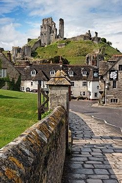 Corfe Castle overlooking the Bankes Arms Hotel in the village below.