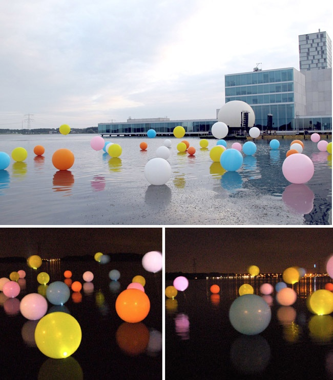 'Bubblegum', a whimsical and colorful installation by Merijn Hos and Renée Reijnders. The piece features 50 balloons around one metre in diameter across the Weerwater in Almere, Netherlands. At night, LED lights are inserted into the balloons to create a magical hue-filled glow.