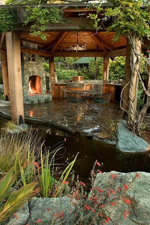 Amazing outdoor space- Pergola with fireplace and water. Rustic, rather than jungle, themed though. And add a ceiling fan! Perfect :)