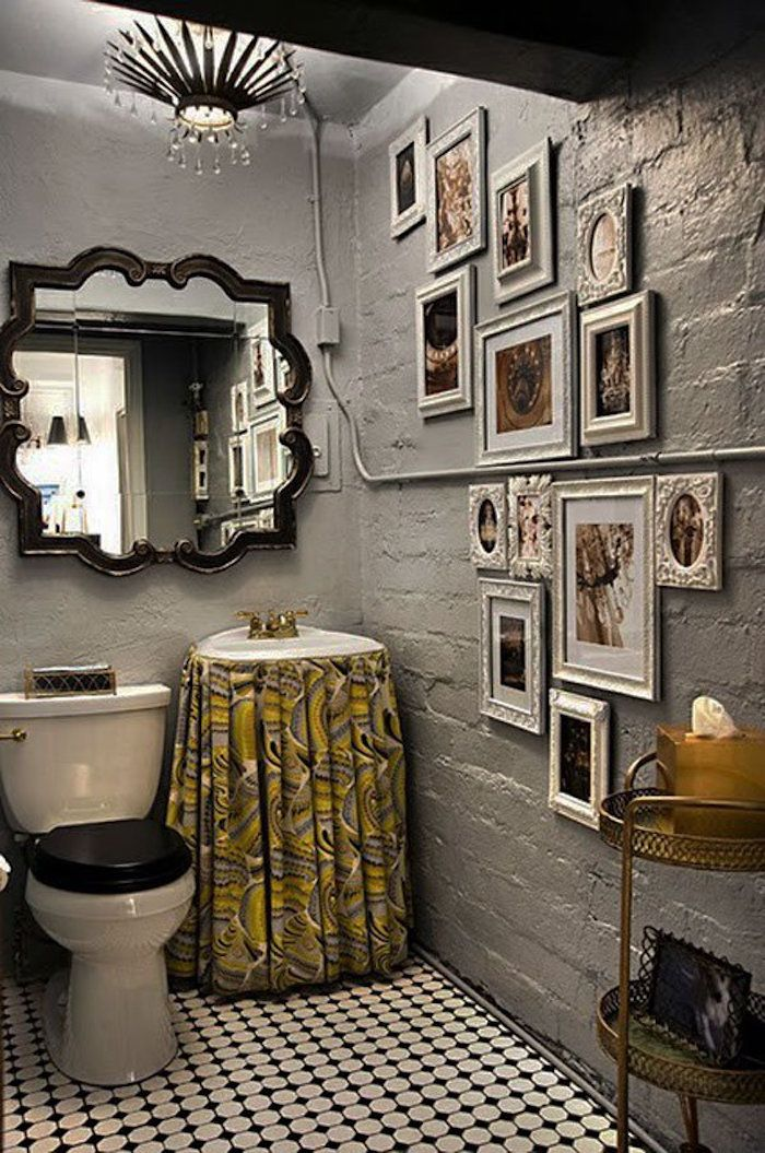 toilet with rough walls painted in grey, with a large baroque wall mirror, one wall decorated with many photos in different white frames, white and black tiled floor, classic toilet seat, and sink with yellow and grey patterned curtain