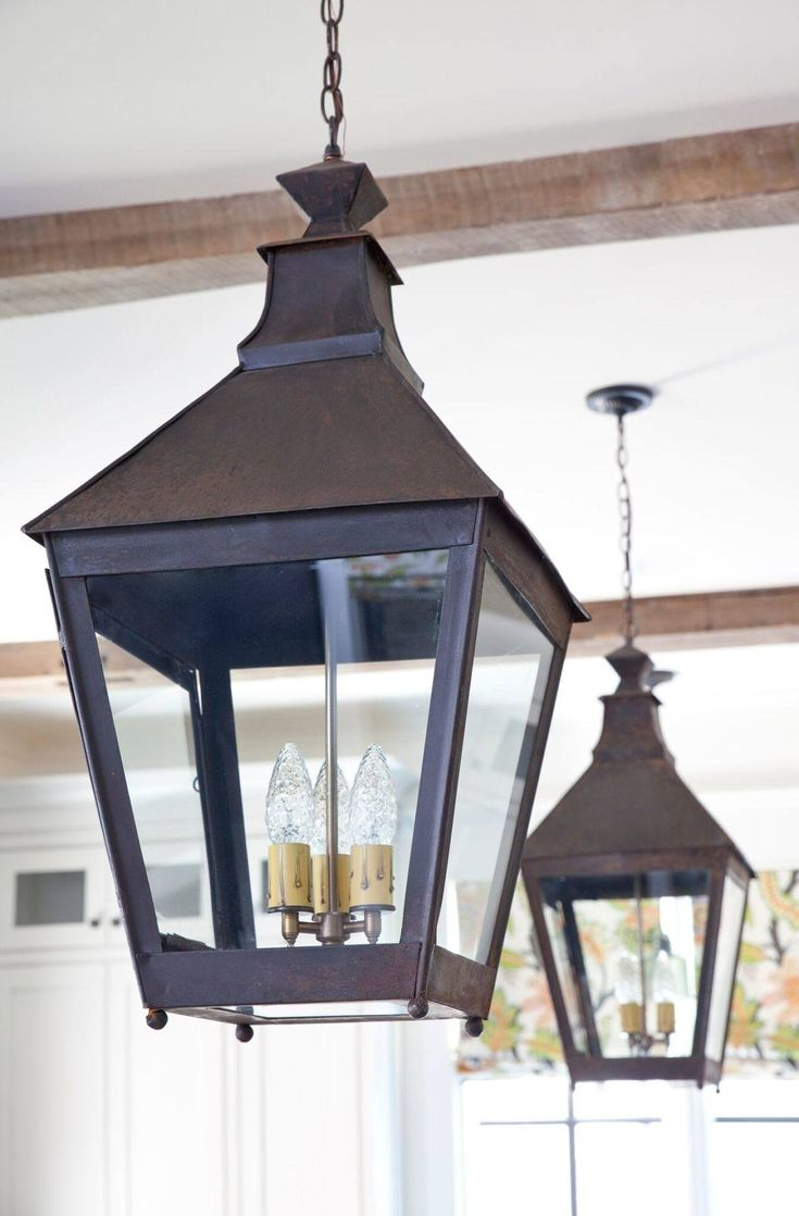 """Antique lanterns and ceiling beams help """"age"""" the kitchen in a good way."""