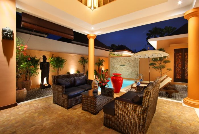 Suasana ruang tamu dengan kolam renang di malam hari