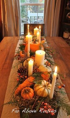 Evergreen sprigs and white candles of varying sizes are the backbone of this autumn tablescape. For an easy winter update, remove the gourds and add pinecones, berries, and red fruit.