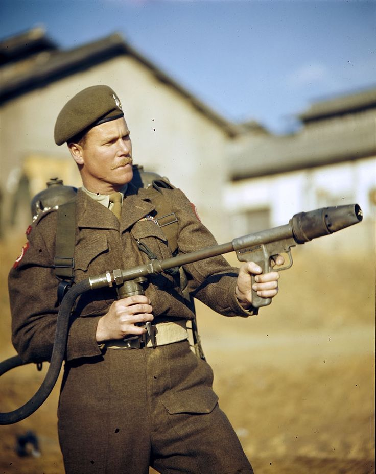 Captain Andy Foulds demonstrates how to hold a flamethrower. (Bill Olson, LAC – PA142711)