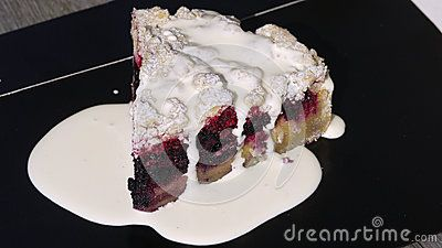 A cake of rapsberries with vanilla cream on a gray bench.