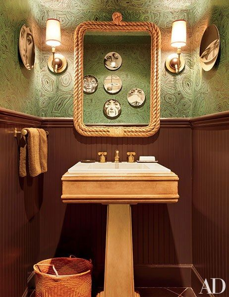 A selection of Fornasetti plates hangs atop a malachite-print Fornasetti wallpaper by Cole & Son in Nate Berkus's Greenwich Village powder room, in New York City. Sconces from Circa Lighting flank a custom-made rope mirror designed by Berkus. | archdigest.com