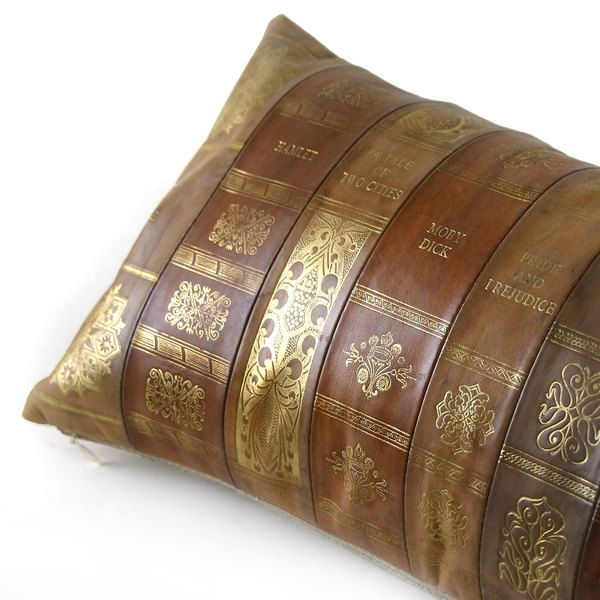 As Shown: Novel Idea Pillow Size: 9 x 18 inches Material: Leather Color: Multicolored   Description: Cozy up with the classics in warm sepia tones embossed with the titles of some of the greats in literature including Moby Dick, Robinson Crusoe, The Great Gatsby, A Tale of Two Cities, War and Peace, Hamlet, Pride and Prejudice, The Grapes of Wrath, and Ulysses. Artisans piece leathers and emboss with gold foil by hand, then back with natural linen or leather. Fitted with a feather and down…