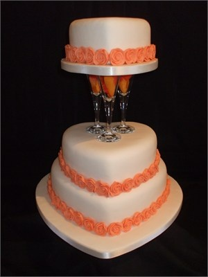 3 Tier Heart Shaped Wedding Cake Decorated with Orange Roses and glass separators.