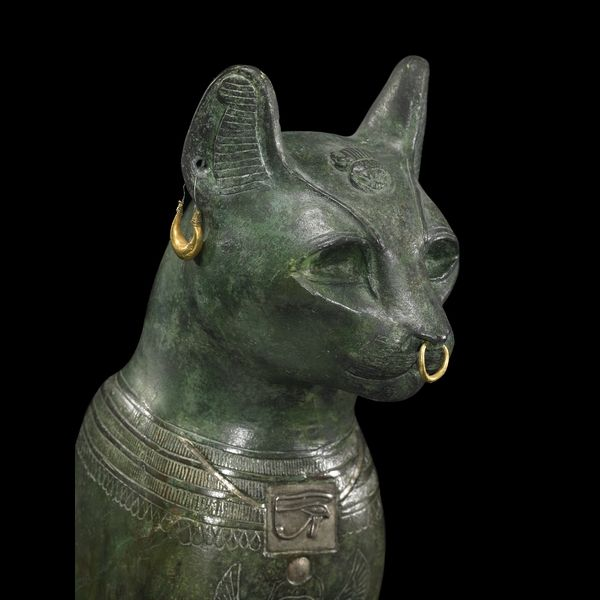 Bronze figure of a seated cat.    From Saqqara, Egypt: Late Period, after 600 BC.  The sacred representation of the goddess Bastet    The domesticated cat is probably associated more with ancient Egypt than any other culture in the world. This cat is a particularly fine example of the many statues of cats from ancient Egypt. It has gold rings, a silvered collar round its neck and a silver protective wedjat eye amulet.