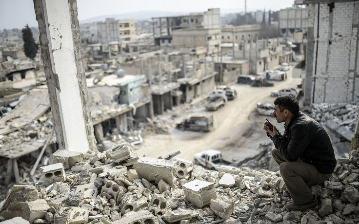 A Kurdish man talks with a radio as he checks the eastern part of the Syrian border town of <span>Kobani</span> on January 28.