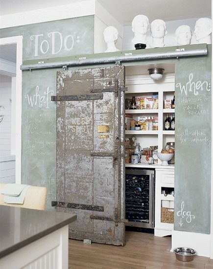 This pantry, photographed for Cottage Living, is pretty sweet. Yes, there's a chalkboard wall, a wine fridge and ample wig storage. But there's also a super cool sliding door!