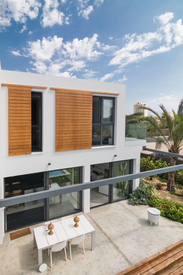 Grandes #ventanas con #persianas vistas #correderas de #madera #natural y #pavimento #continuo de #hormigón #fratasado