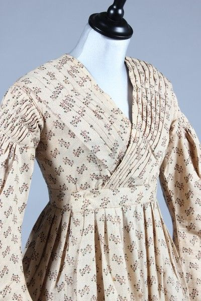 A printed challis day dress and fichu, late 1830s, the cross-over bodice with diagonal pleats, shirred and gathered upper sleeves