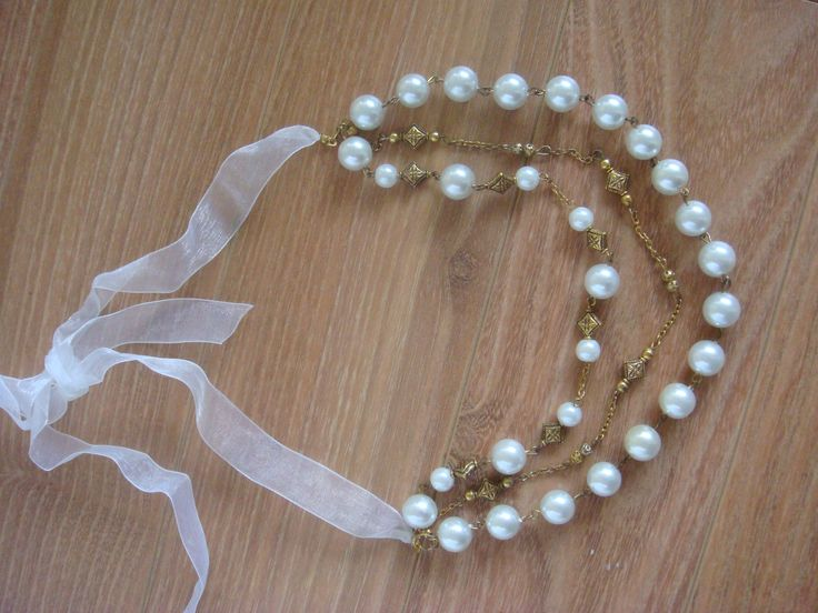 White pearl necklace with white bow for tying