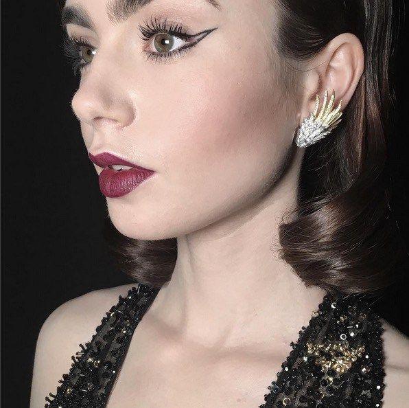 Uno dei trucchi più chiacchierati in assoluto è il look noir di Lily Collins, che ha abbinato a labbra scure un incredibile cat-eye negative space. Sul profilo Instagram della makeup artist Fiona Stiles è specificato il rossetto usato: si tratta del Rouge Absolu di Lancôme in Berry Noir (prezzo: 34€