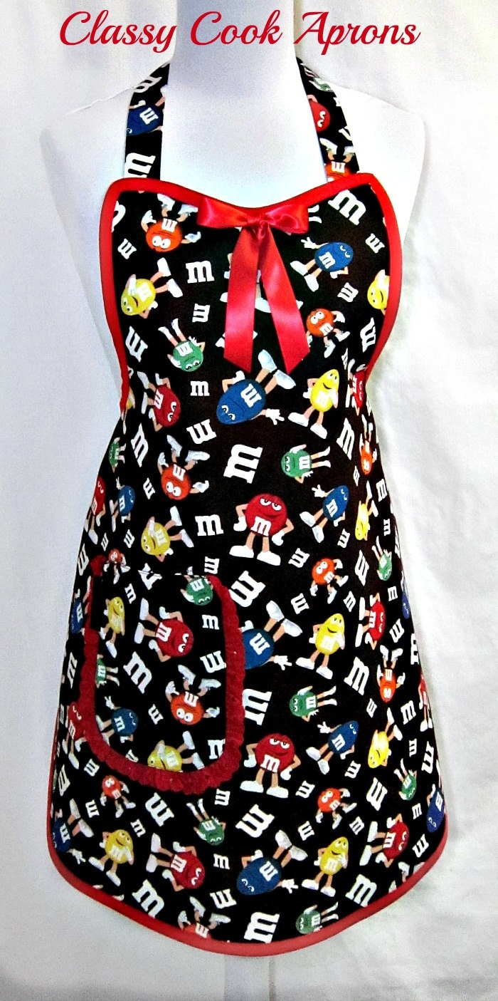 Apron in M Characters shows the different color M's in familiar poses on a candy wrapper brown background. Too cute and Calorie-Free! The color palette includes Red, Blue, Green, Orange & Yellow on yummy Milk Chocolate. For a touch of panache, we trimmed it in Lipstick Red, added a large lined right hand pocket trimmed in pretty red eyelet, and a Red satin bow at center bib. And Ta-Da! Let's cook up something Fun!