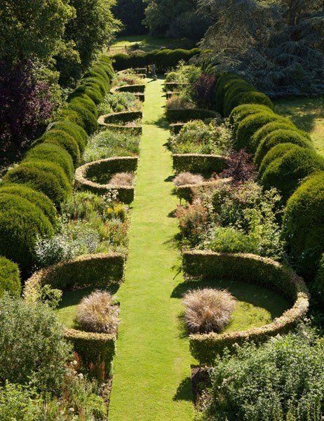 Though one of the leaders of the New Perennial movement of naturalism in the garden, the late Henk Gerritsen, was also a master of highly artful interventions. At Waltham Place in Berkshire—the home of Orcillia and Nicholas F. Oppenheimer, chairman of the De Beers diamond-mining company—magnificent horseshoe-shaped hedges made of beech add rhythm to the Long Border. Each is accented by panaches of Stipa arundinacea grass, while connecting beds brashly combine interesting weeds (burdock…