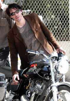 Keanu Reeves wears an Iggy & The Stooges shirt with his wife, a dirty motorcycle