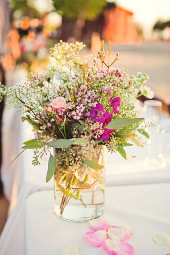 Great idea for a relatively inexpensive DIY wedding centerpiece. Notice the wide variety of fillers and greens with a splash of color from flowers. Baby's Breath, Seeded Eucalyptus, Wax Flower are the base fillers with just a small splash of color coming from the pink/hot pink flowers.