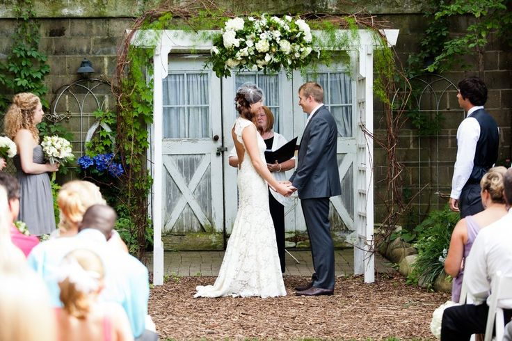 a rustic outdoor wedding ceremony under an arbor