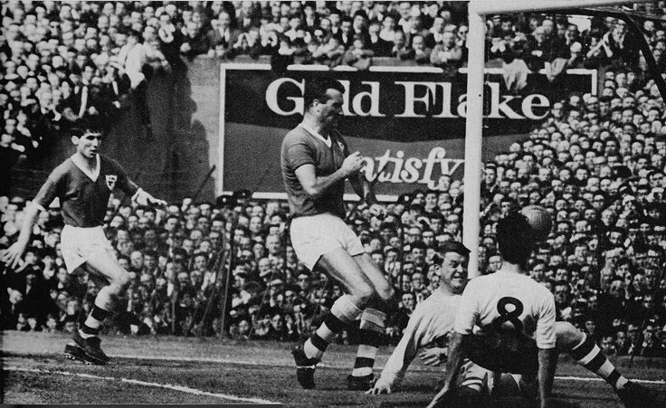 24th May 1964. England inside forward Jimmy Greaves slips between Ireland's Noel Cantwell and goalkeeper Noel Dwyer to score the third goal, Dalymount Park, Dublin.