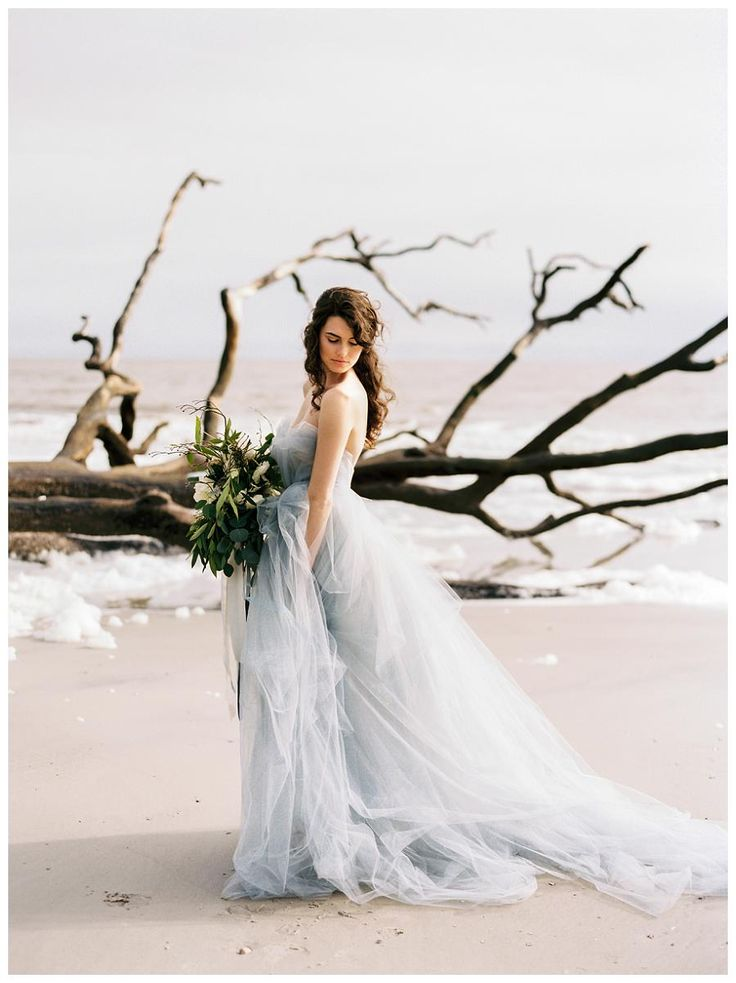 Bridal portrait by the sea. Blue wedding dress by Carol Hannah, bouquet by Em. Creative Floral, hair and makeup by Bride's Side Beauty. Image by Perry Vaile Photography.