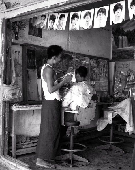 Western and traditional styles mix easily in Burma, as seen in this Mrauk U barbershop. The man's skirt, tied from a sheet of cloth, is called a longyi.