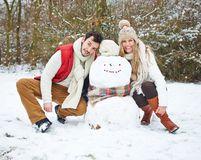 Coppie felici con il pupazzo di neve nell'inverno Fotografie Stock