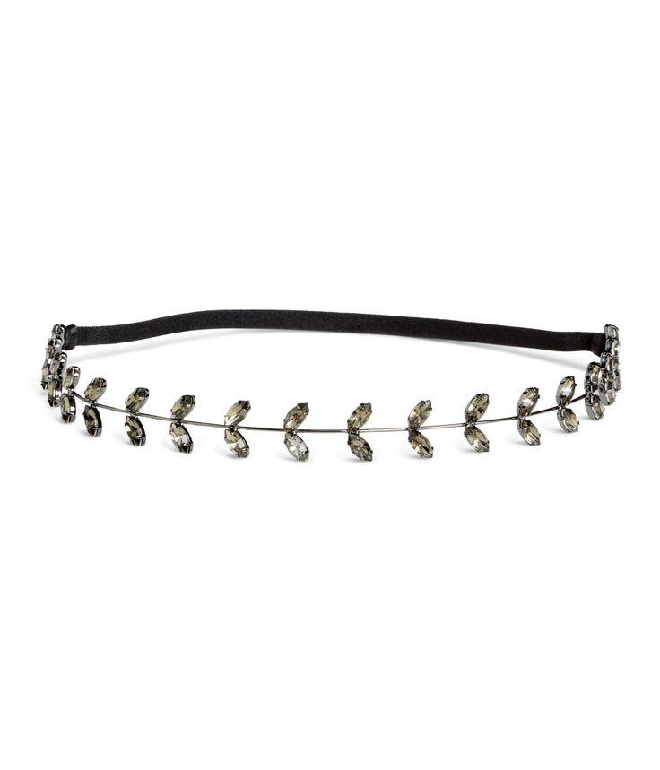 Sølv. Et hårbånd i metall dekorert med fasettslipte perler i plast. Elastikk bak.