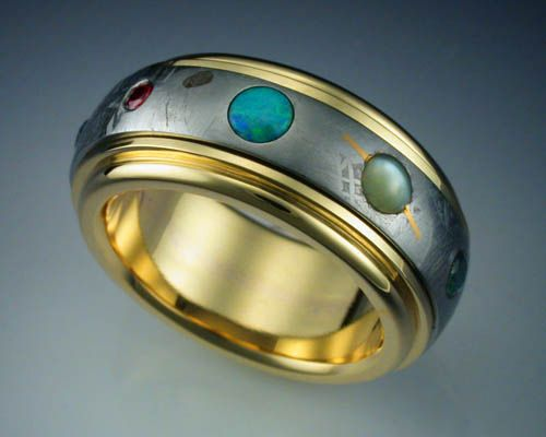 This ring features a complete band of Gibeon Meteorite framed and mounted in an 18k gold band. The meteorite has been etched with nitric acid to reveal the characteristic patterns, or Widmanstatten figures, of iron meteorites, and set with 9 gemstones representing the planets of our Solar System.