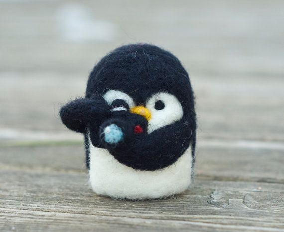 Needle felted penguin (about 2.75 inches tall, 2 inches wide) holding a small needle felted camera (securely attached to wings). Please note: