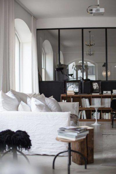 canapé blanc recouvert de lin dans un salon avec verrière type atelier