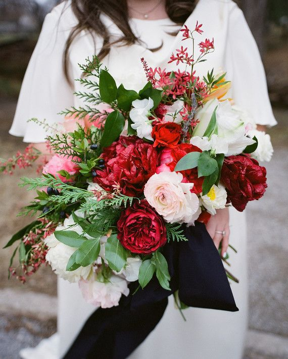 At her Christmas-themed wedding, this bride clutched a bouquet by Poppy Lane Design that included David Austin garden roses, smilax, ranunculus, festival bush, tulips, poppies, astilbe, peonies, and amaryllis.