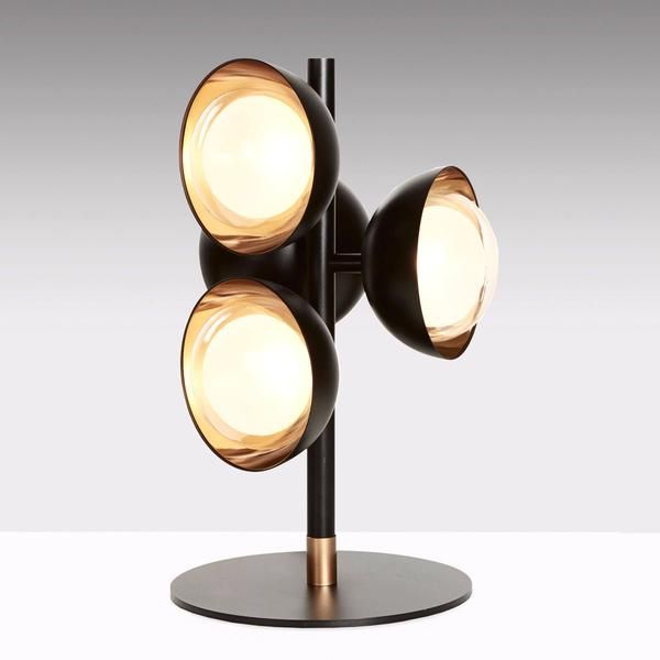 The Muse table lamp is at once dramatic and refined. The Italian design features four sleek black shades, each finished internally with brushed brass or copper and containing a borosilicate glass diffuser.