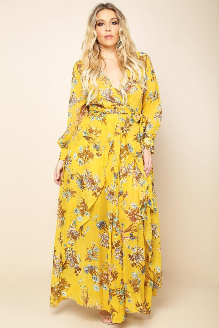A plus size maxi dress with a wrapped V-neckline and long sleeves. Features a belted waistline and an open front overlay. Floral print all over.