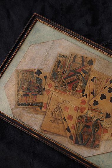 アート・デ・トロカデロ、描かれたトランプ-watercolor painting frame 額縁は100年以上前の古いお品、背当てを見ると今の今まで幾度か飾る絵を入れ替えた跡が。わざと?折り目を付けた台紙に直接ペンで枠線を、双頭でないクラシックな各トランプ絵柄。画像左端に位置する従者の意味のクローバーはアーサー王伝説の円卓の騎士の一人ランスロット、一番上のスペードの女王はギリシア神話の戦いの女神アテナ。その中でもセンター下、半分潜った形で描かれているカードが興味深い。今はペンスに換わったイギリスの貨幣単位、1シリングとあり、英国では1960年まで娯楽であるトランプには税金が課せられていたそう。スペードのエースにはトランプ製作業者がお国に納税済みですよ、というマークを付けた、、という豆情報。額縁上部に付いたリング状金具で壁掛け出来、ガラスが入っております。