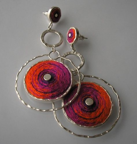 Earrings on a stick made of silver 930 Silver forms filled embroidery in the overlapping colors of magenta and orange. Silver hammered, frosted.