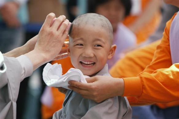A novice monk smiles as he gets his head shaved by a Buddhist monk during a ceremony to celebrate the upcoming birthday of Buddha at the Jogye temple in Seoul April 25, 2011.   REUTERS/Truth Leem