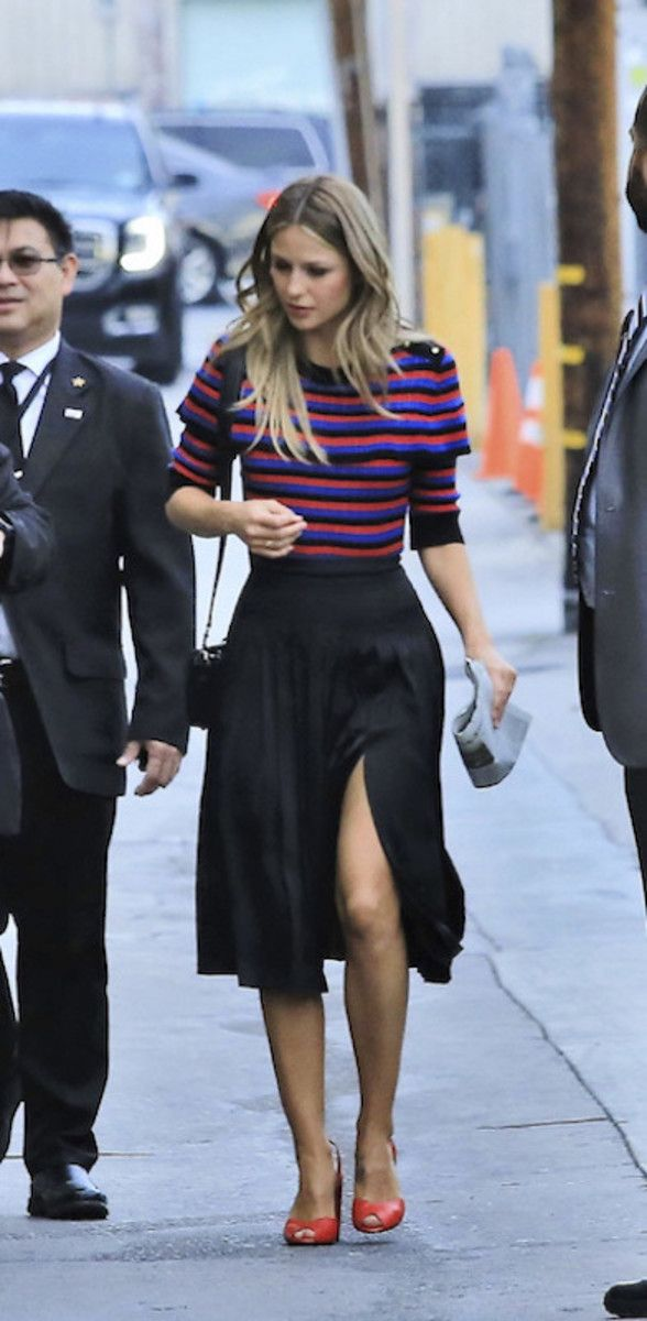 Melissa Benoit wearing a multicolor striped ruffle sweater, black silk midi skirt with a slit, black crossbody bag, and red pumps