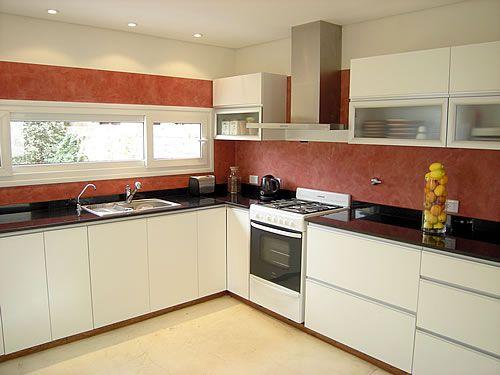 Mueble de cocina realizado a medida en melamina, blanco, con cantos ABS y tirador buña. Sistema Slow en cajones. Sistema auto frenante en puertas.