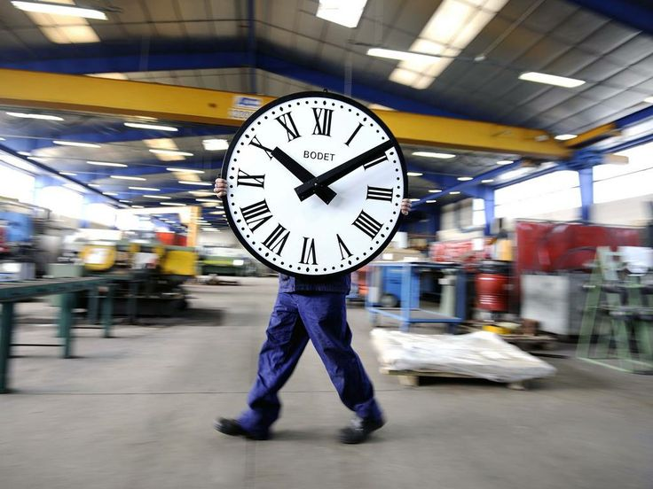 An employee of the Bodet Company carries a clock at the plant of Trementines, France