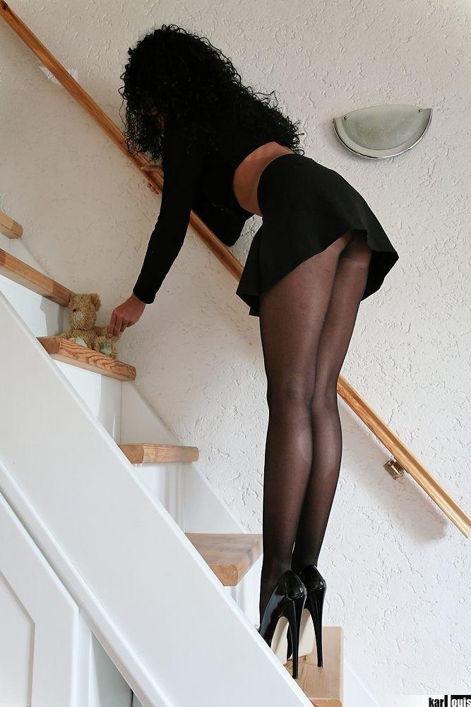 женщина стоит нагнувшись в черных колготках и в платье торгпредстве целую