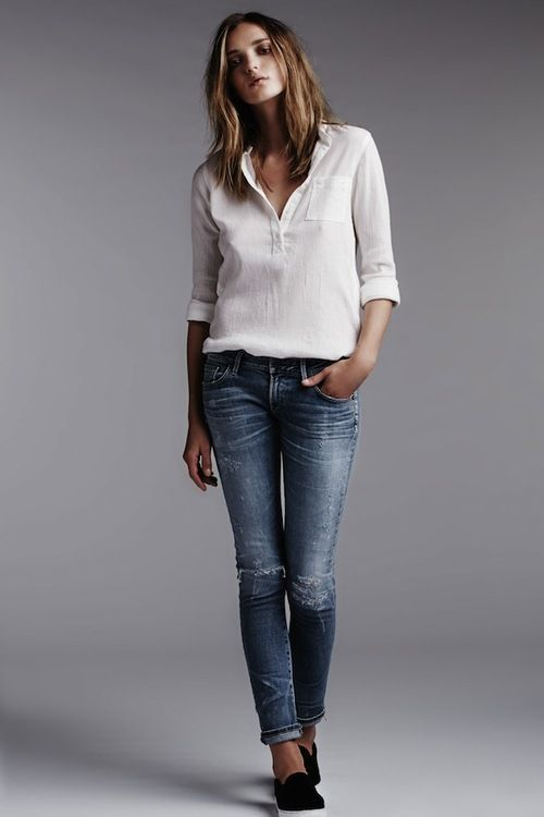 Shop this look on Lookastic: https://lookastic.com/women/looks/white-henley-shirt-navy-ripped-skinny-jeans-black-slip-on-sneakers/9185   — White Henley Shirt  — Navy Ripped Skinny Jeans  — Black Slip-on Sneakers