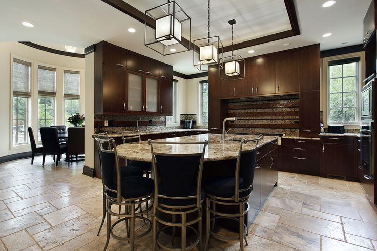 U-shaped kitchen with dark wood cabinets and large granite-topped island with seating on one end.  Tray ceiling includes dark wood molding.