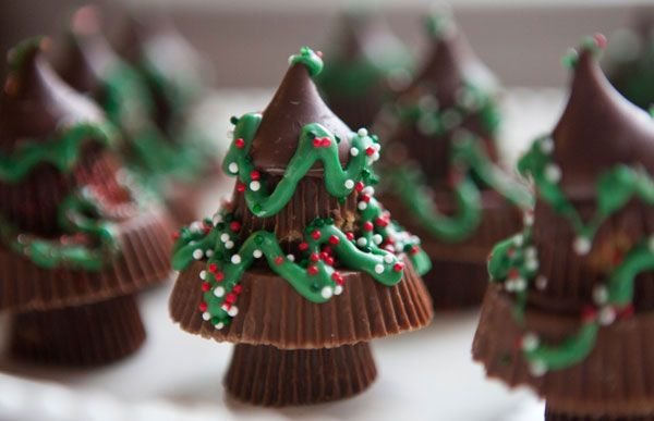Peanut Butter Christmas Trees: Four pieces of candy, frosting, and sprinkles are all you need to build these teeny chocolate trees.