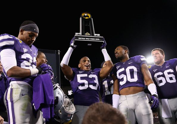 2013 Buffalo Wild Wings Bowl Champs....Linebacker Blake Slaughter #53 of the Kansas State Wildcats celebrates with the Buffalo Wild Wings Bowl trophy after defeating the Michigan ...