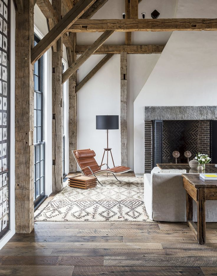 Wood beams and black steel windows in a living room with modern rustic decor
